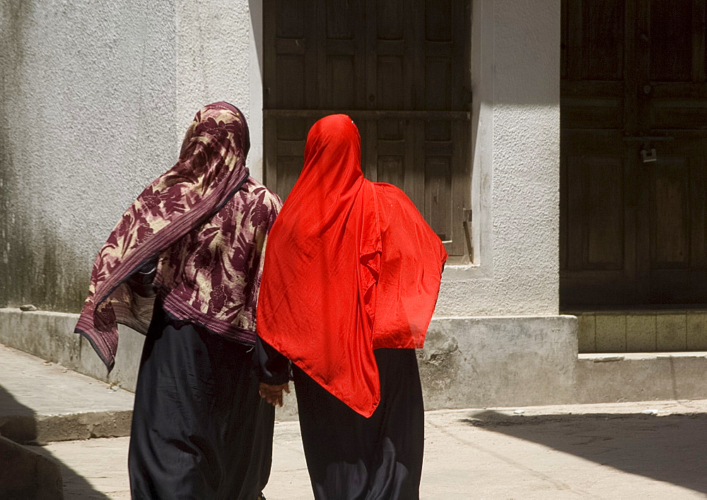 Women wearing colourful headscarves walking in Stone Town, Zanzibar, Tanzania, East Africa, Africa