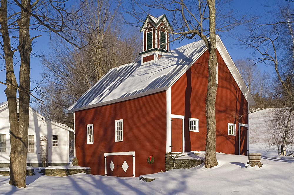A traditional red painted barn surrounded by snow, Vermont, New England, United States of America, North America