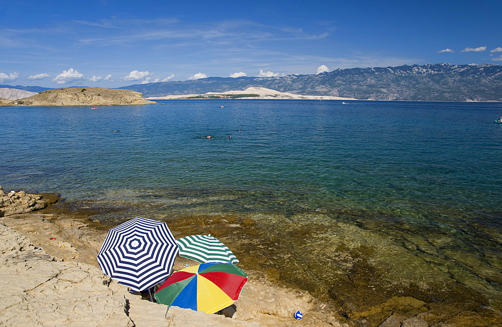 Beach umbrellas by the sea at San Marino, island of Rab, Kvarner region, Croatia, Europe