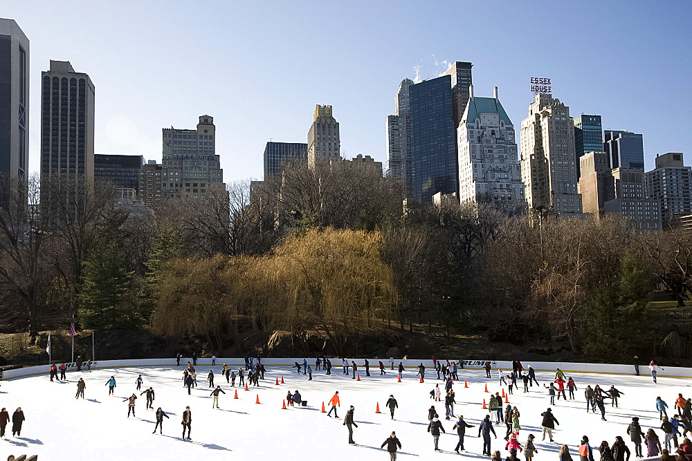 Skaters on the Woolman Rink in Central Park with the skyline behind, New York City, New York State, United States of America, North America