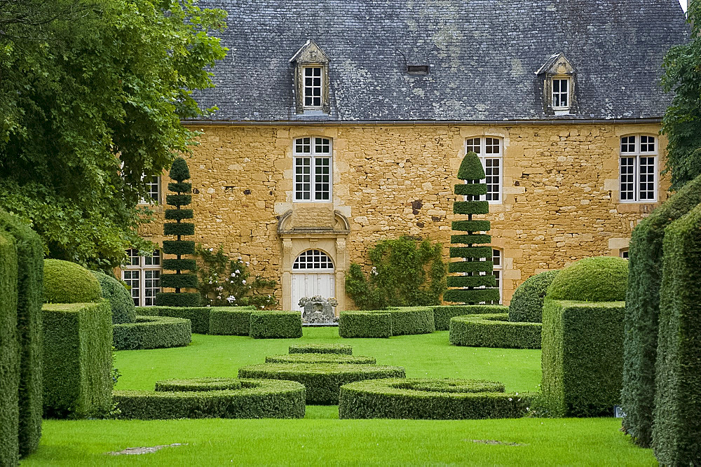The manor house surrounded by topiary in Les Jardin du Manoir D'Eyrignqac in Salignac, Dordogne, France, Europe