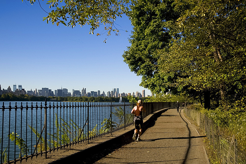A jogger on the track around the reservoir in Central Park and the city skyline in the background, New York City, New York State, United States of America, North America