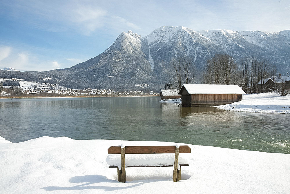 A snow covered bench facing Hallstatter See and the surrounding mountains near the town of Hallstatt, Austria, Europe