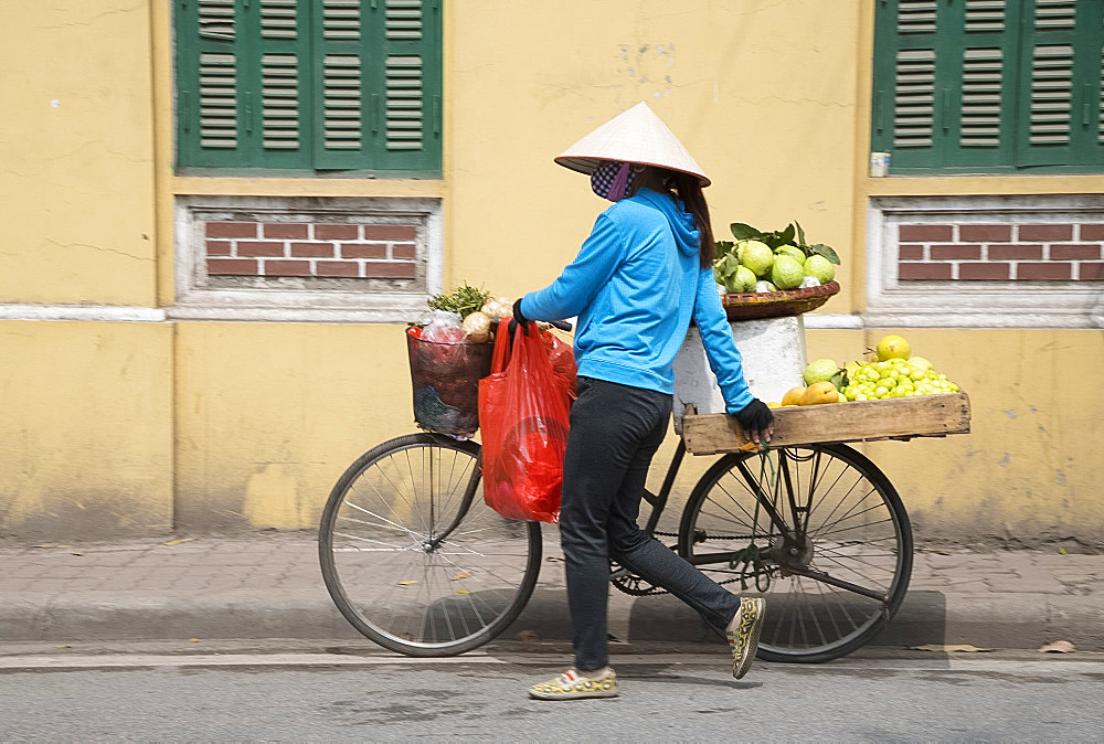 A woman selling fruit from her bicycle in Hanoi, Vietnam, Indochina, Southeast Asia, Asia