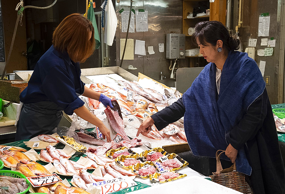 A Japanese woman buying fish in the Omicho Market. Kanazawa, Ishigawa, Japan, Asia