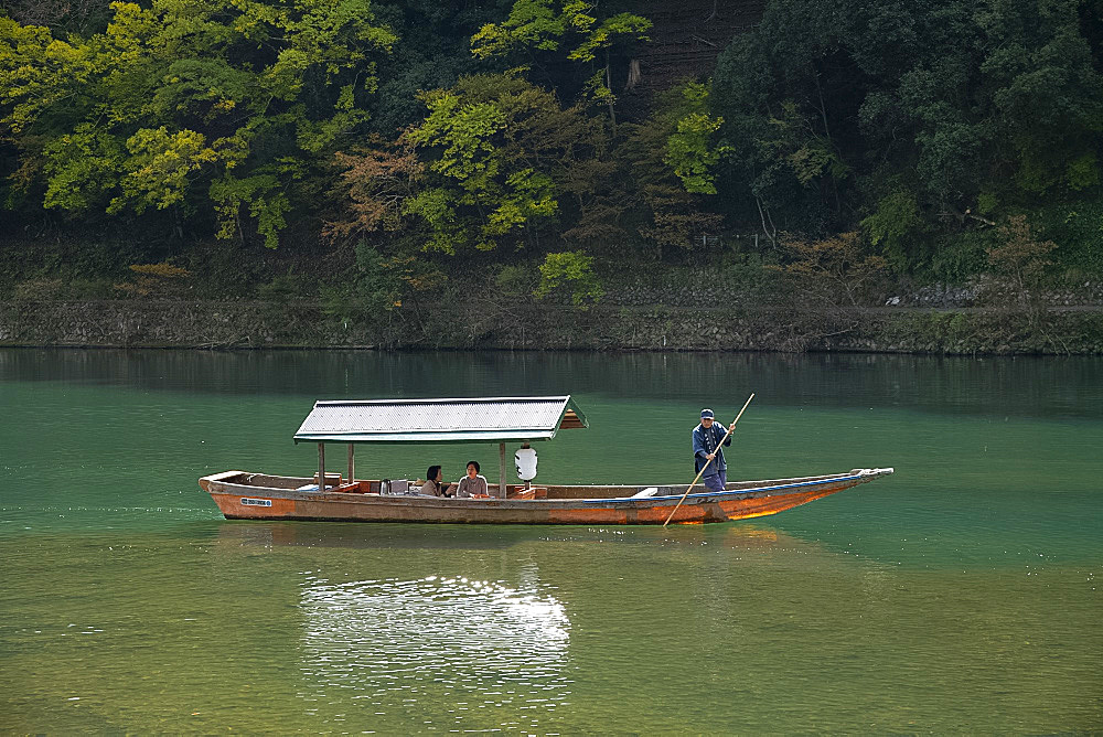 Tourists sightseeing in a small wooden boat on the Oi River in the Arashimaya region outside Kyoto, Japan, Asia