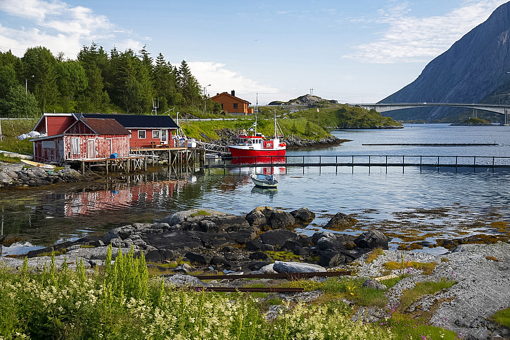 A fishing boat and dock houses near Kakern Bridge, Ramberg, Lofoten Islands, Norway, Europe