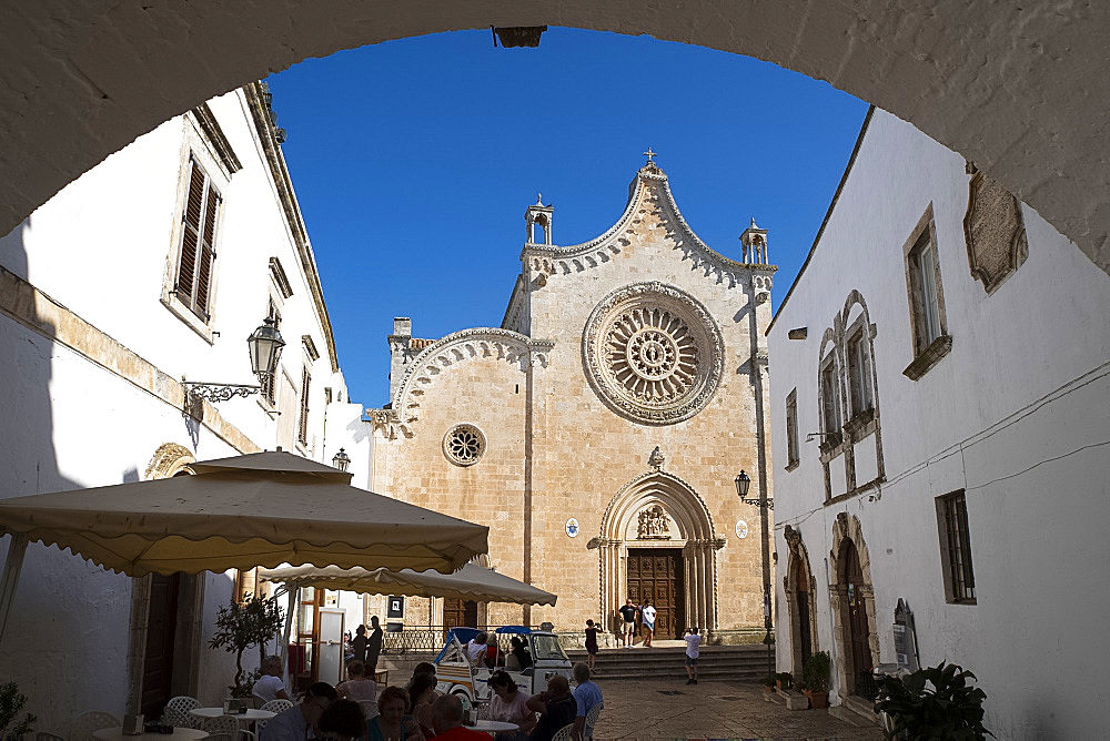 A view through an arch to the rose window on the Cathedral of Santa Maria dell Assunzione in Ostuni, Puglia, Italy, Europe