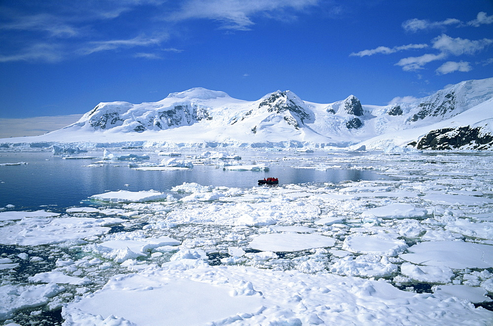 Seascape with ice and snow, and people ice cruising in zodiac, Antarctic Peninsula, Antarctica, Polar Regions