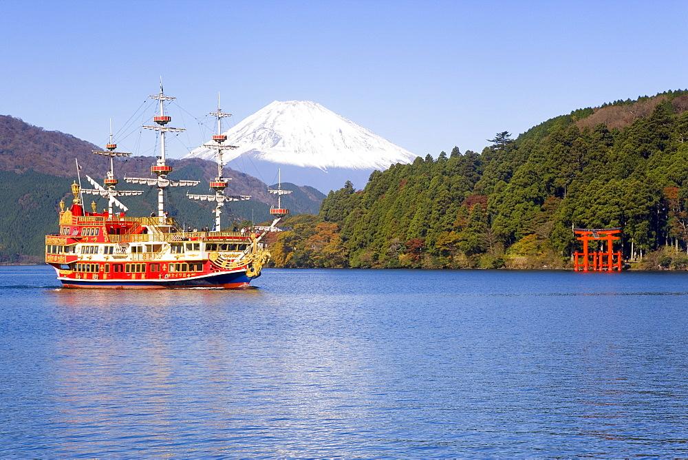 Tourist pleasure boat on lake Ashino-ko with the red torii gates of Hakone-jinja rising from the lake and snow capped Mount Fuji beyond, Fuji-Hakone-Izu National Park, Hakone, Central Honshu (Chubu), Japan, Asia