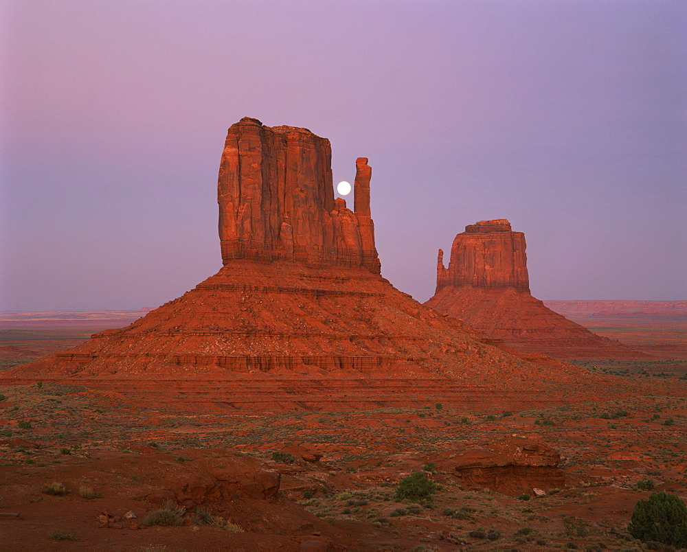 The moon above the rock formations known as The Mittens in the Navajo Reservation in Monument Valley, Utah, United States of America, North America