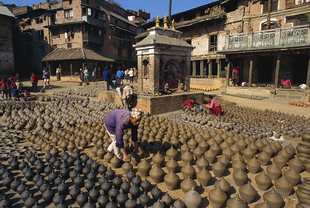 Man with rows of clay pots drying in Potters Square at Bhaktapur near Kathmandu, Nepal, Asia