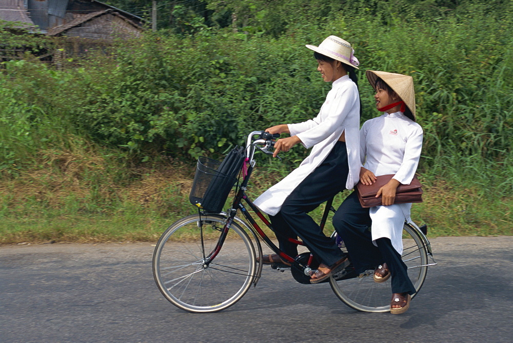 Two school girls in traditional Ao Dai on a bicycle in the Mekong Delta region south of Ho Chi Minh City in Vietnam, Indochina, Southeast Asia, Asia
