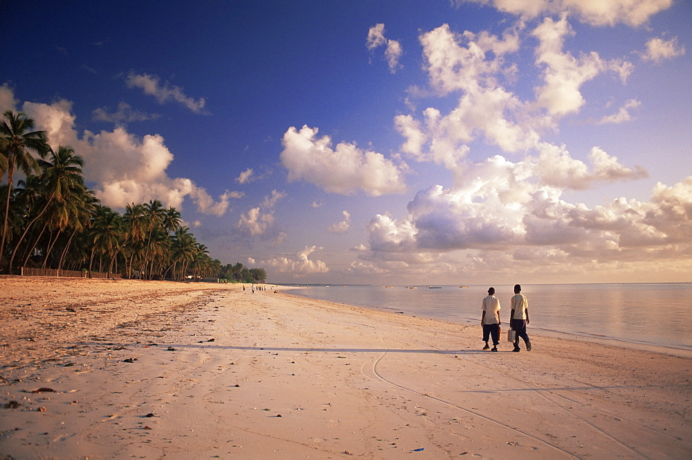 Two boys walking to school along the beach at Jambiani, Zanzibar, Tanzania, East Africa, Africa