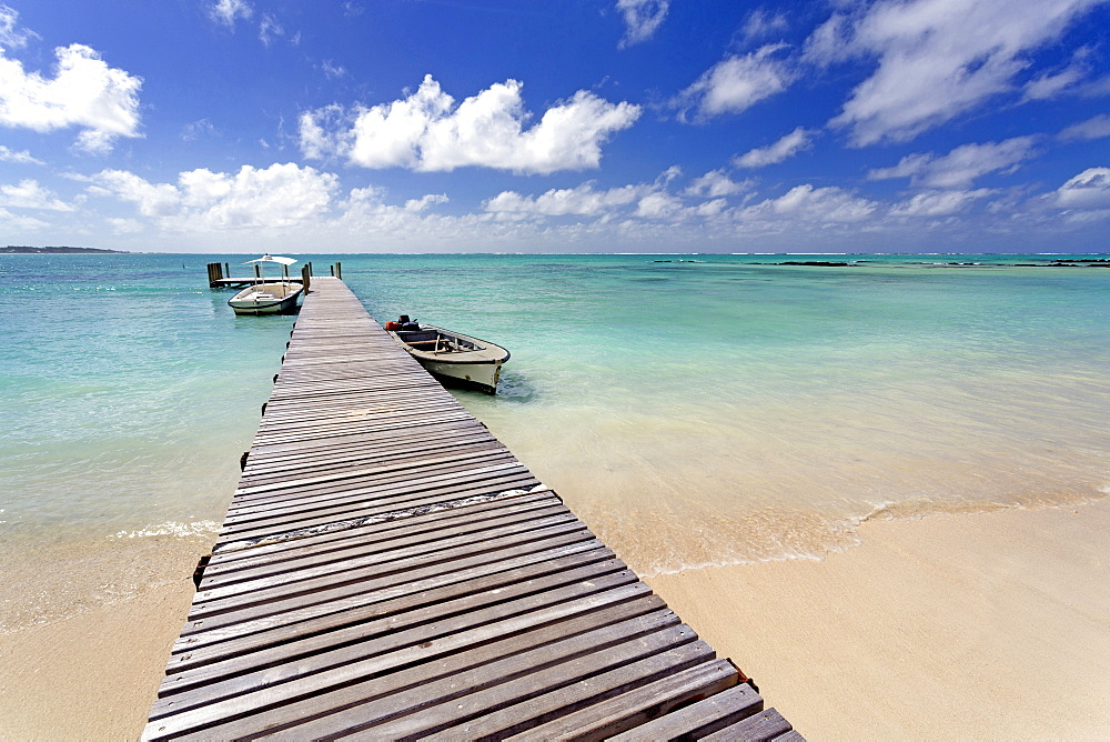 Wooden jetty with boats tied to it stretching out into the Indian Ocean off an idyllic beach on Ile Aux Cerfs, Mauritius, Indian Ocean, Africa
