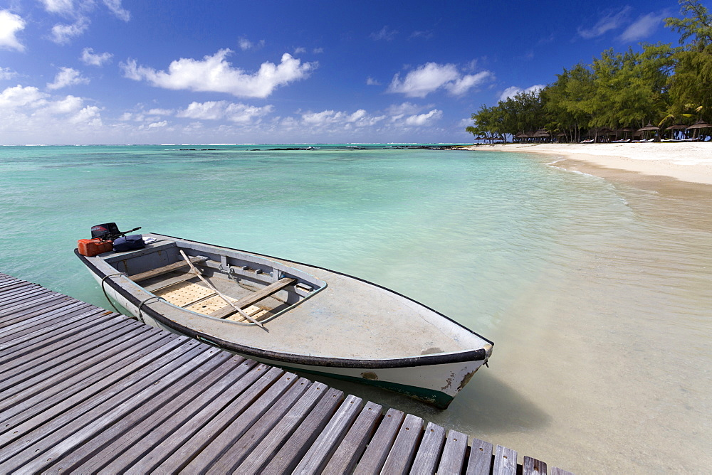 Wooden jetty with a boat tied to it, stretching out into the Indian Ocean off an idyllic beach on Ile Aux Cerfs, Mauritius, Indian Ocean, Africa