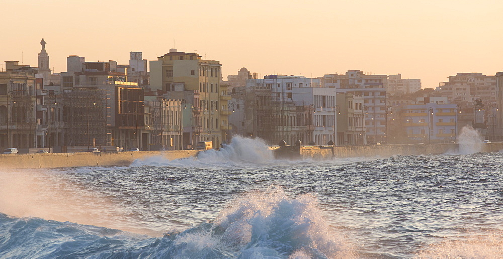 Buildings along The Malecon bathed in soft evening sunlight with large waves crashing against the sea wall, The Malecon, Havana, Cuba, West Indies, Caribbean, Central America