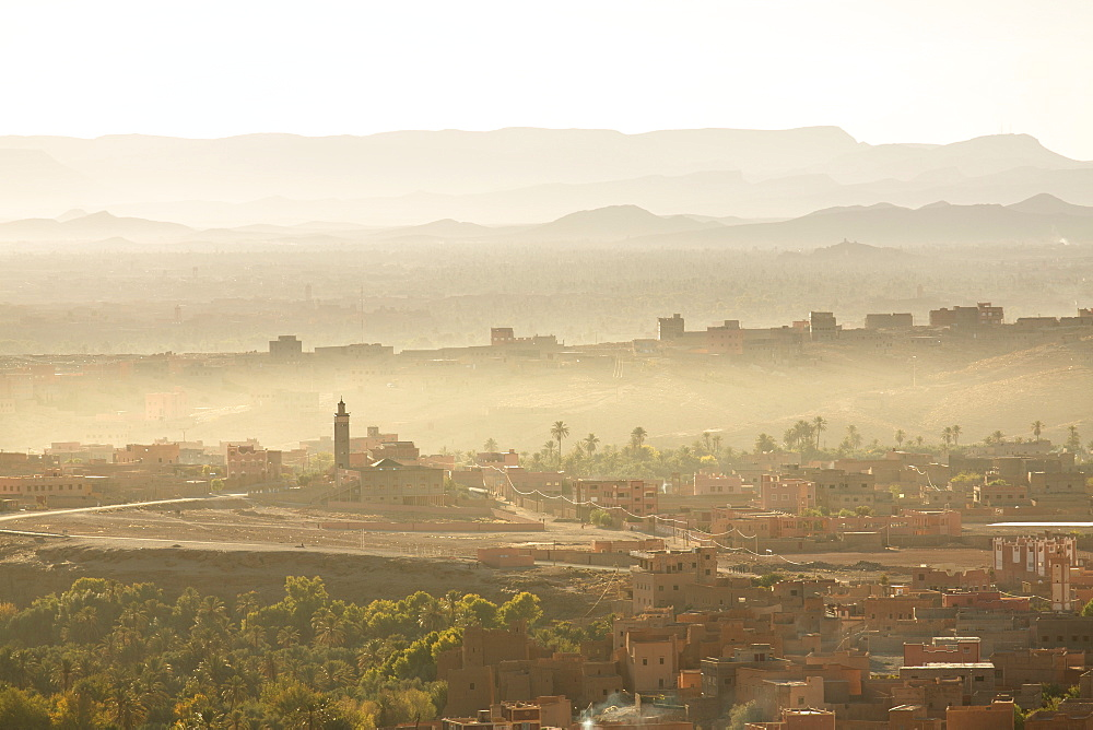 View over the town of Tinerhir soon after sunrise showing smoke rising from the streets and traditional houses bathed in sunlight, Tinerhir, Sousse-Massa-Draa, Morocco, North Africa, Africa