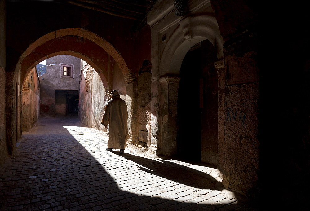 Local man wearing a djellaba casting a long shadow in a sunlit street in the Kasbah, Marrakech, Morocco, North Africa, Africa