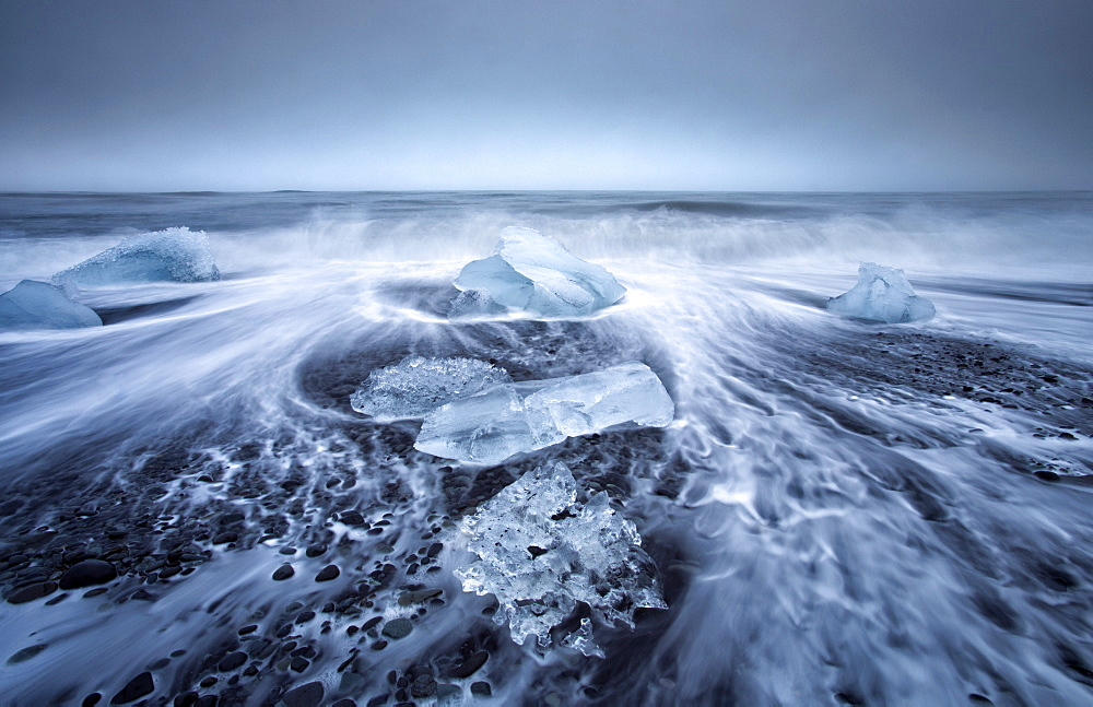 Jokulsa Beach on a stormy day, where icebergs from nearby Jokulsarlon glacial lagoon flow into the North Atlantic and are washed back onto the black volcanic sand beach, on the edge of the Vatnajokull National Park, South Iceland, Iceland, Polar Regions