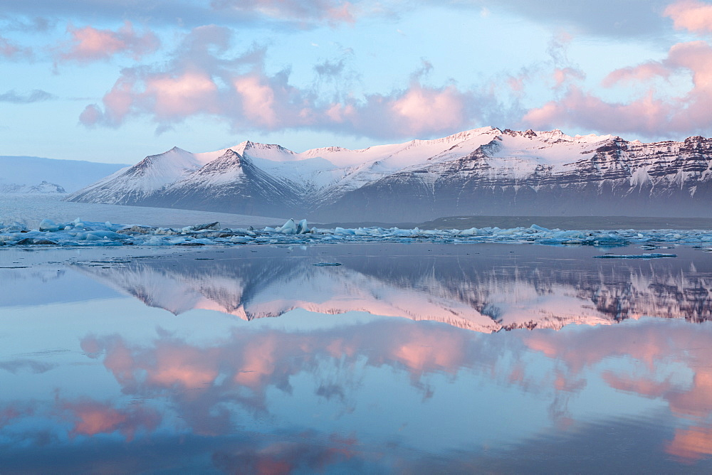 Panoramic view across the calm water of Jokulsarlon glacial lagoon towards snow-capped mountains and icebergs bathed in the last light of a winter's afternoon, at the head of the Breidamerkurjokull Glacier on the edge of the Vatnajokull National Park, South Iceland, Iceland, Polar Regions