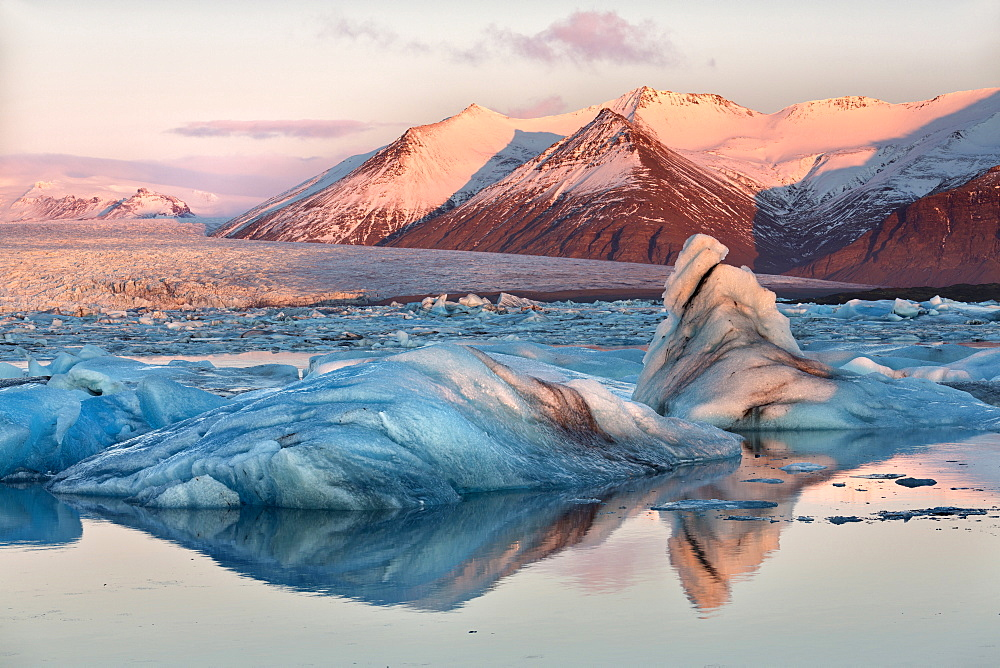 View across the calm water of Jokulsarlon glacial lagoon towards snow-capped mountains and icebergs bathed in winter morning light, at the head of the Breidamerkurjokull Glacier on the edge of the Vatnajokull National Park, South Iceland, Iceland, Polar Regions