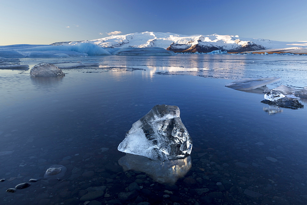 View of icebergs on Jokulsarlon, a glacial lagoon at the head of the Breidamerkurjokull Glacier, with some icebergs illuminated by the afternoon winter sun, on the edge of the Vatnajokull National Park, South Iceland, Iceland, Polar Regions