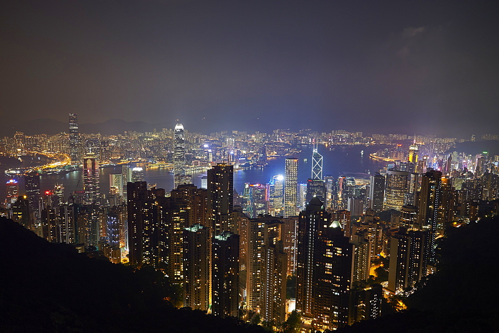 View at night of central Hong Kong and Victoria Harbour from Victoria Peak, looking toward Kowloon in background. China, Asia