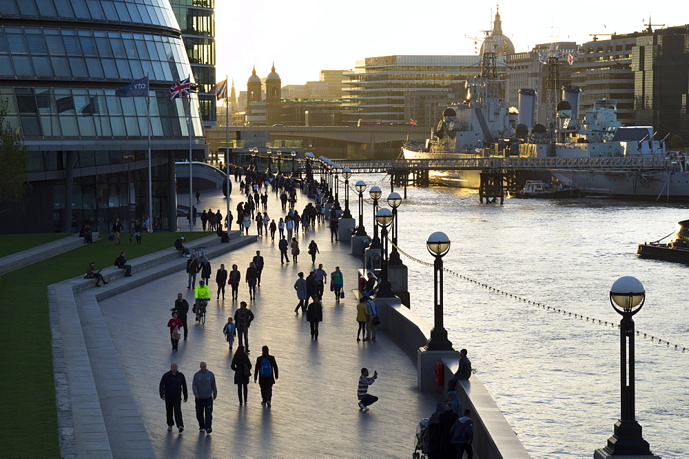 Pedestrians silhouetted on More Place riverfront with City Hall and HMS Belfast behind, London, England, United Kingdom, Europe