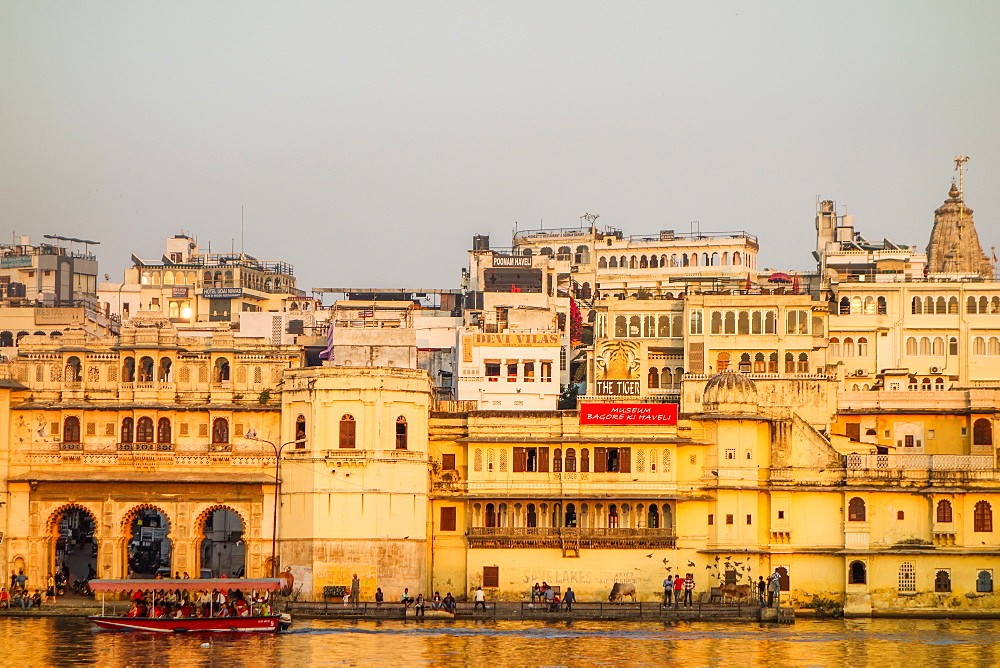 Old building facades, boat in foreground, City Palace side, Lake Pichola, Udaipur, Rajasthan, India, Asia