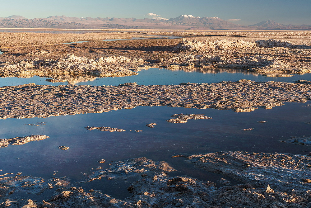 Salt residue piled up by Laguna Chaxa, Atacama Salt Flats, with snow-capped volcanoes, near San Pedro de Atacama, Chile, South America