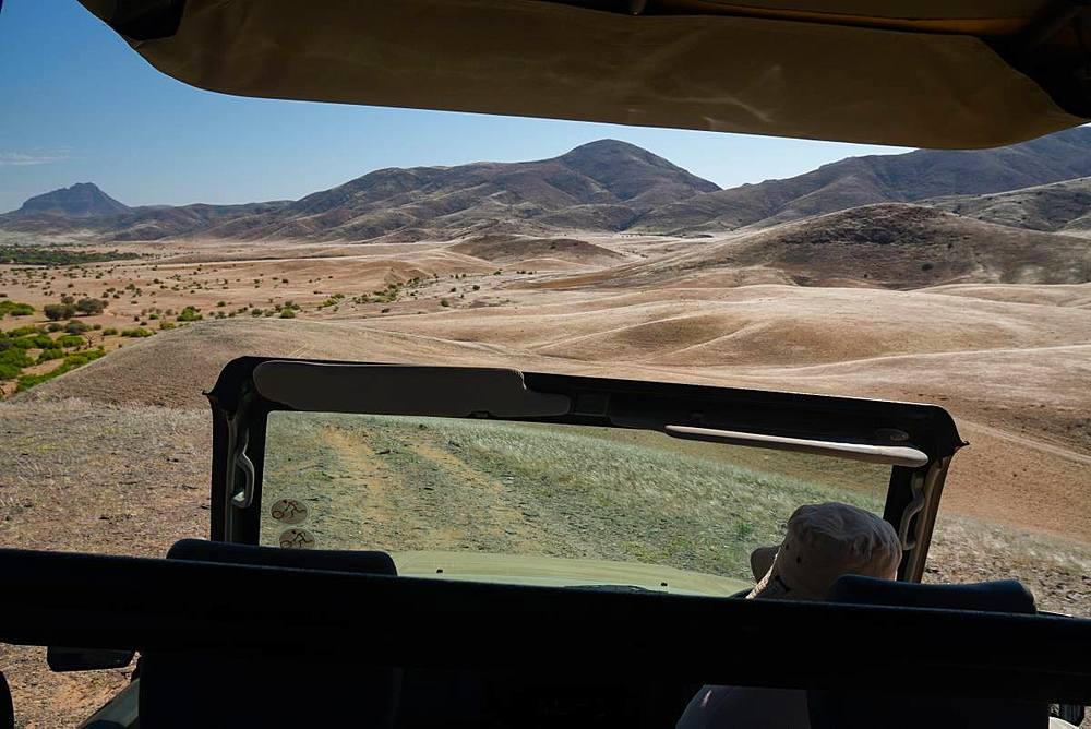 View over Hoarusib Riverbed from inside a safari vehicle, mountain range in background, Puros, north of Sesfontein, Nambia, Africa