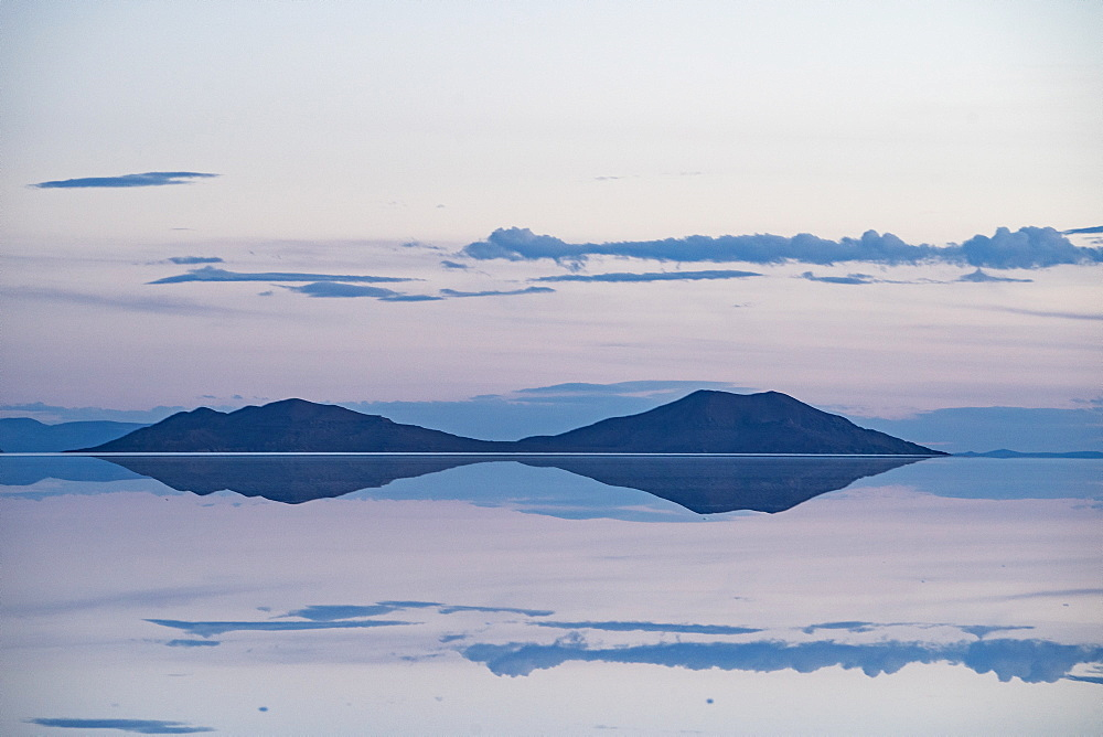 Pastel-coloured beauty of salt flats reflecting the clouds and mountains after rainfall just after sunset, Uyuni, Bolivia