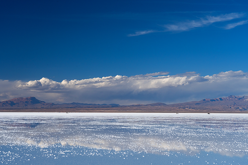 The beauty of the salt flats reflecting the clouds and mountains after rainfall, three 4WD vehicles in the distance, Uyuni, Bolivia, South America