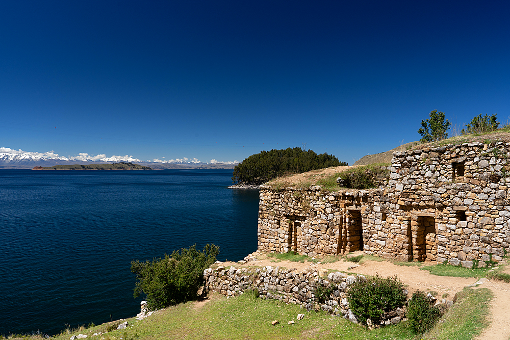 View across deep blue Lake Titicaca with the ruins of the Inca Pilocaina Sun Temple, from Sun Island, Lake Titicaca, Bolivia