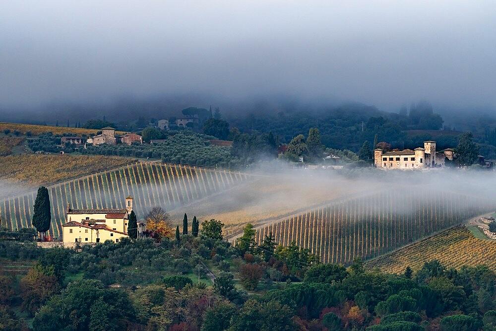 Castello di Gabbiano across a misty valley, church in foreground, San Casciano, Tuscany, Italy - 450-4467