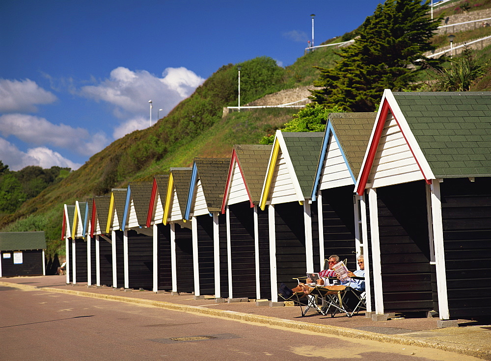 Relaxing on the Promenade outside a colourful beach hut below the cliff in early summer sunshine. West Cliff, Bournemouth, Dorset, England, United Kingdom, Europe
