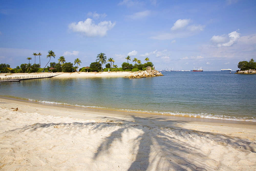 Empty sheltered tropical Siloso beach and bay, palm tree shadow on imported sand with man-made island at western end of southern coast, Sentosa Island, Singapore, Southeast Asia, Asia - 586-1460