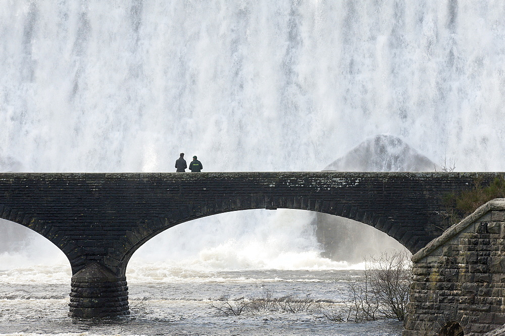 Visitors walk across a bridge as water cascades over the Caban-coch dam, at Elan Valley village near Rhayader in Powys, Wales, United Kingdom, Europe