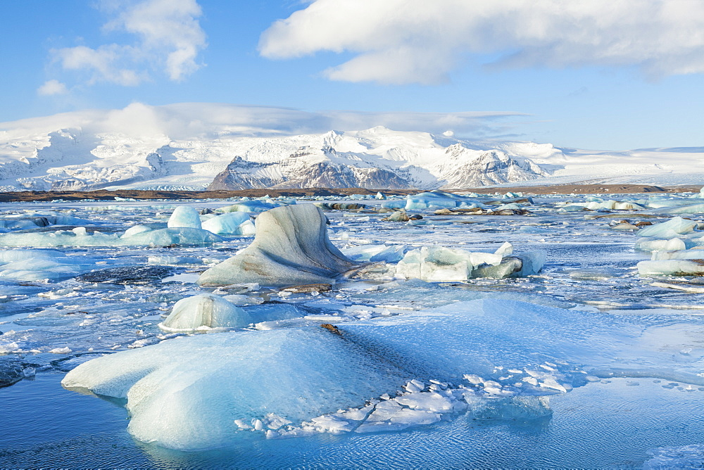 Mountains behind the icebergs locked in the frozen water of Jokulsarlon Iceberg Lagoon, Jokulsarlon, South East Iceland, Iceland, Polar Regions