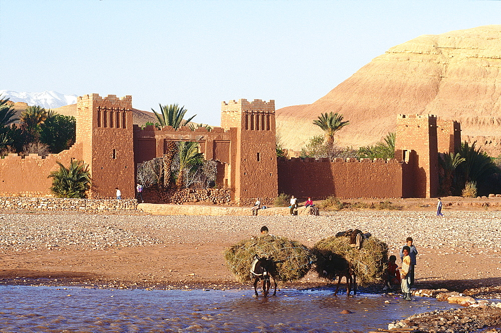Morocco, South, Ouarzazate Region, Ait Benhaddu Ksar Ruins (Ancient Adobe Fortress And Village), Overview On The Ramparts And River (Oued), Peasants Crossing On Donkey)