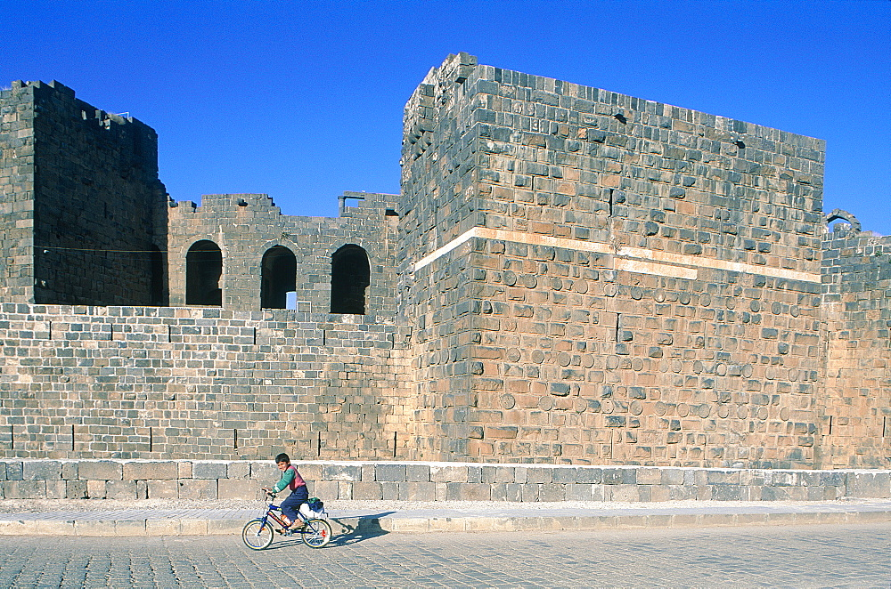 Syria, Haura, Bosra Ancient Roman Capital Of The Arabia Province, Child On A Bike Passing By The Fortess Walls, At Back The Theater