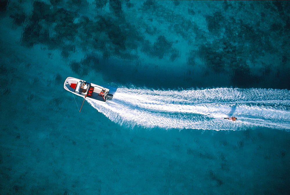 French Polynesia, Windward Islands, Moorea, Aerial Of A Boat Pulling A Waterskier On The Lagoon