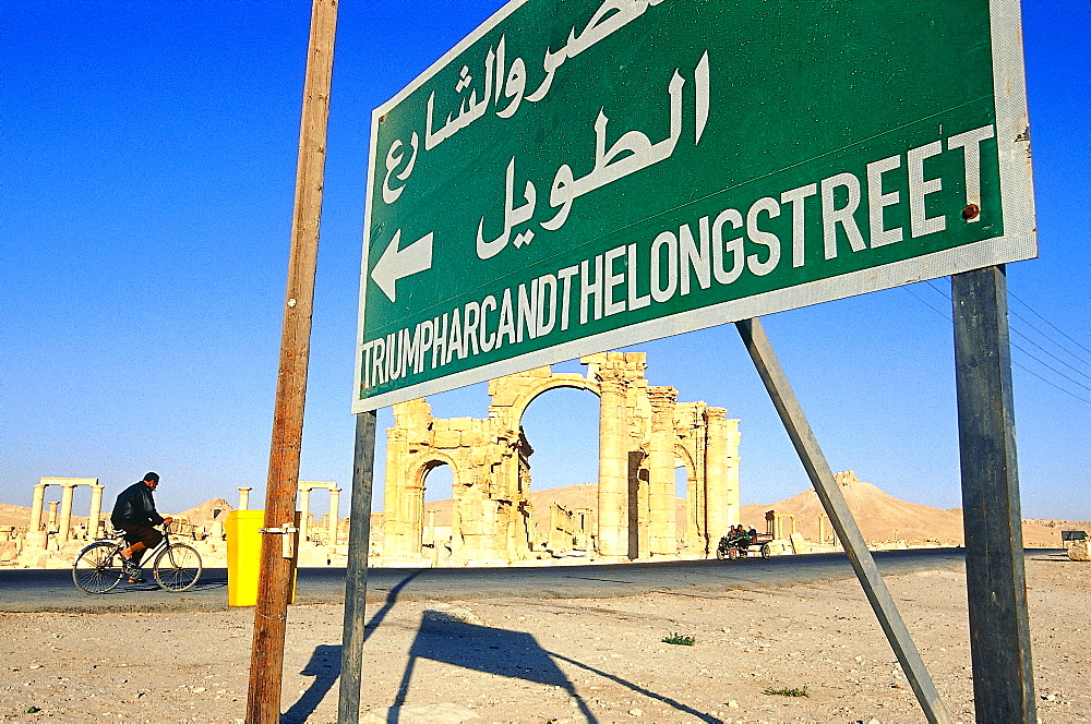 Syria, West Desert, Ruins Of The Ancient City Of Palmyra, Gate Of Roman Cardo Biker And Noticeboard At Fore *** Local Caption ***