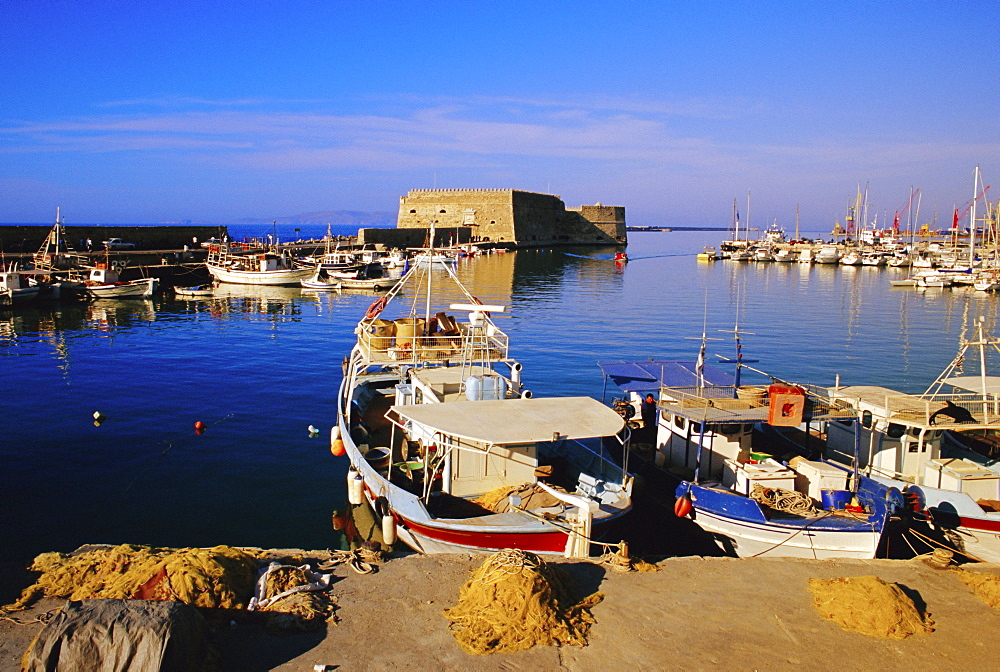 Fishing boats and Venetian fortress at Iraklion old harbour, Crete, Greece