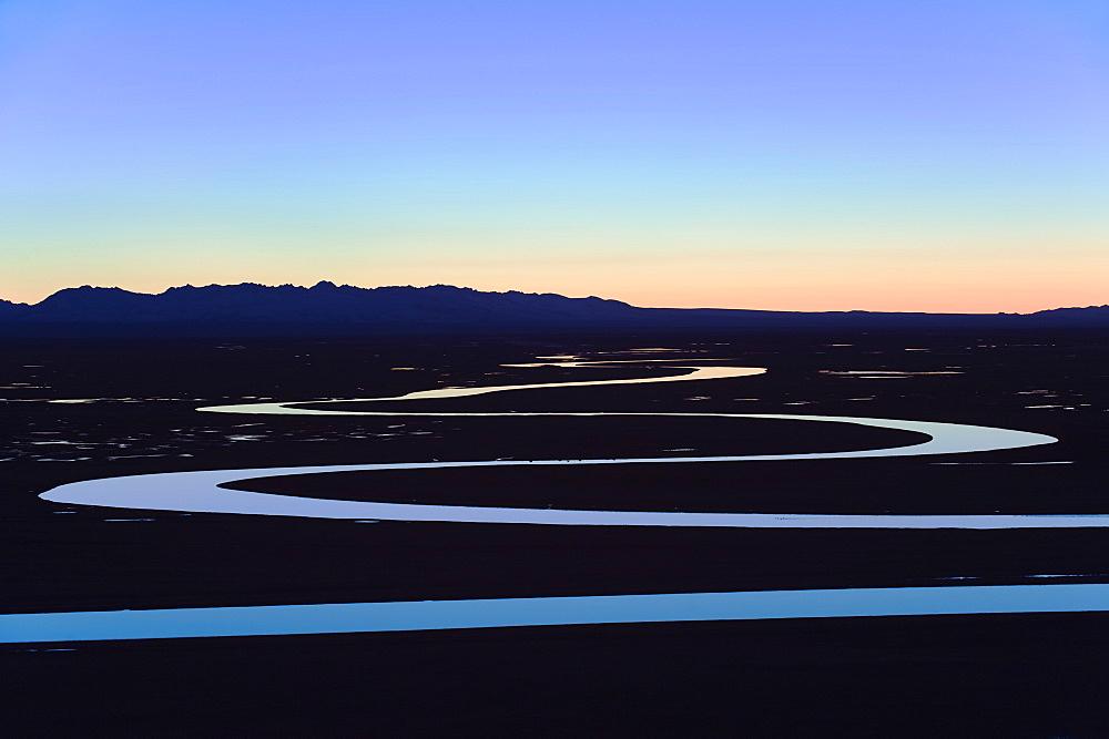 The night sky reflecting in a winding river, Bayanbulak, Xinjiang Province, China, Asia
