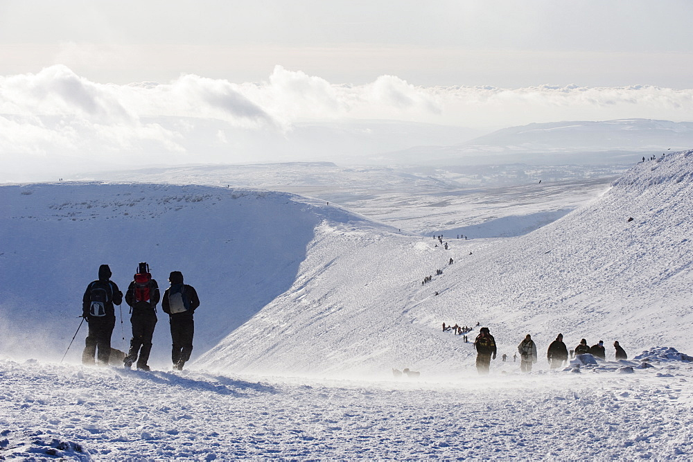 Hikers on snow covered Pen y Fan mountain, Brecon Beacons National Park, Powys, Wales, United Kingdom, Europe