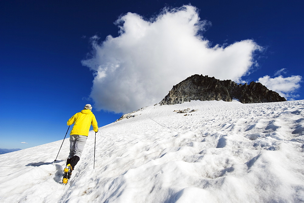 A climber walking up a snowfield, Pico de Aneto, at 3404m the highest peak in the Pyrenees, Spain, Europe