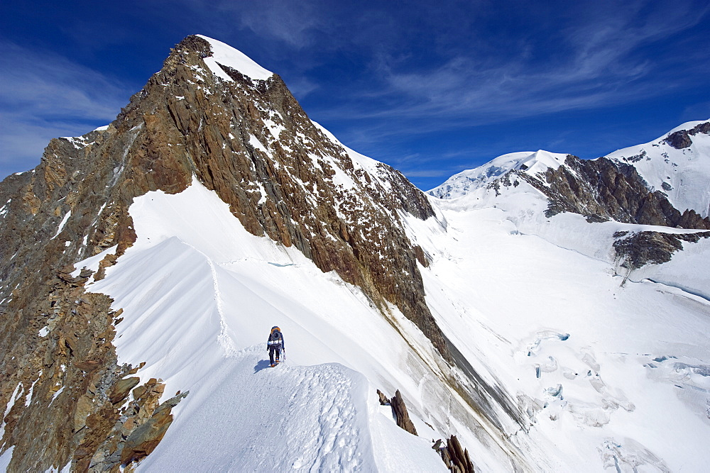 Climber on snow ridge, Aiguille de Bionnassay on the route to Mont Blanc, French Alps, France, Europe