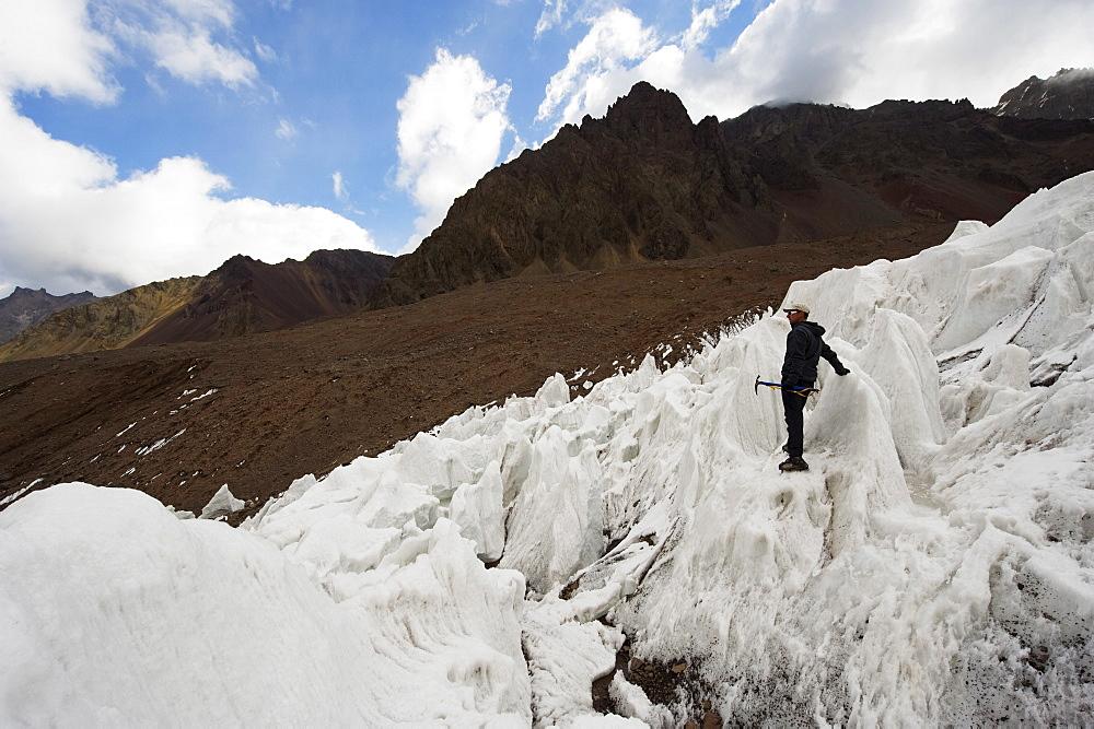 Climber ice climbing on glacier near Plaza de Mulas basecamp, Aconcagua Provincial Park, Andes mountains, Argentina, South America